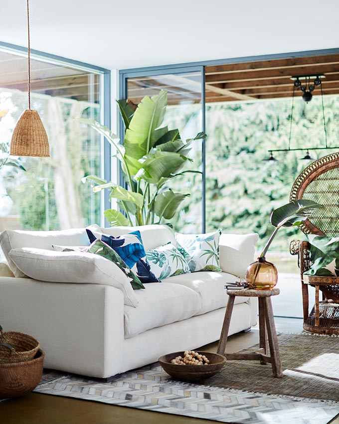 A beautiful white sofa looks great amidst a room with lots of organic accents, along with tropical theme throw pillows and lots of green foliage. Image by DFS Furniture.