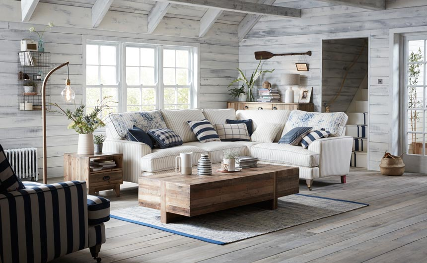 My dream beach house. A beautiful off white living room with a nautical decorating theme, with a white L shaped sofa, and a wooden rustic style coffee table looking all so calming. Image by DFS Furniture.