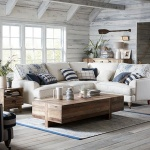 A beautiful off white living room with a nautical decorating theme, with a white L shaped sofa, and a wooden rustic style coffee table looking all so calming. Image by DFS Furniture.