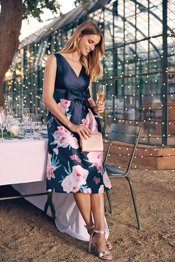 A young woman wearing a blue satin dress, a clutch and silver high heel sandals. The skirt of the dress has a pink floral print. Image by Dorothy Perkins.