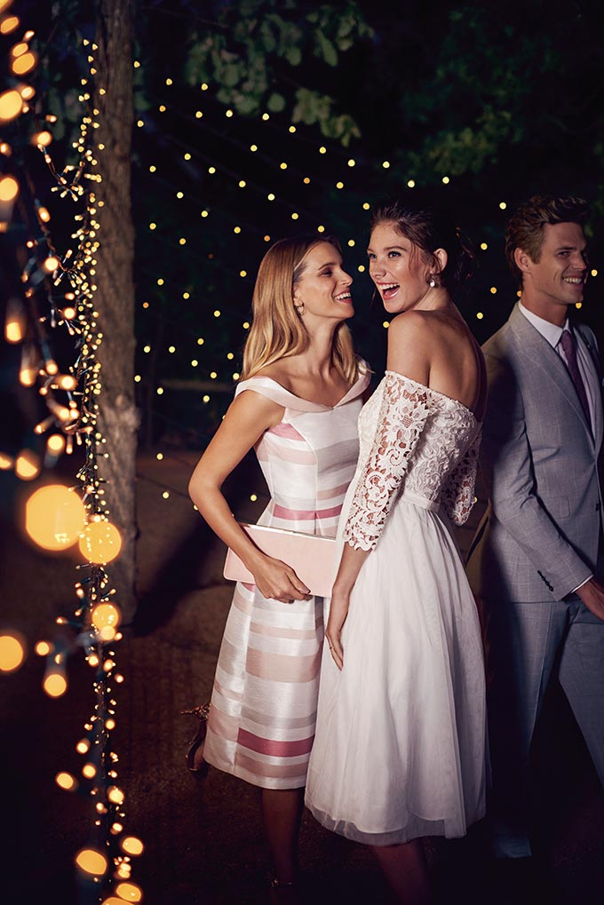 A bride talking to a stylish girlfriend who is wearing a stripe chic dress. A great option is you want to wear a white dress without overshadowing the bride. Image by Dorothy Perkins.