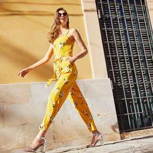 A beautiful model wearing a yellow jumpsuit is walking down a sidewalk by a yellowish building. Image by Dorothy Perkins.