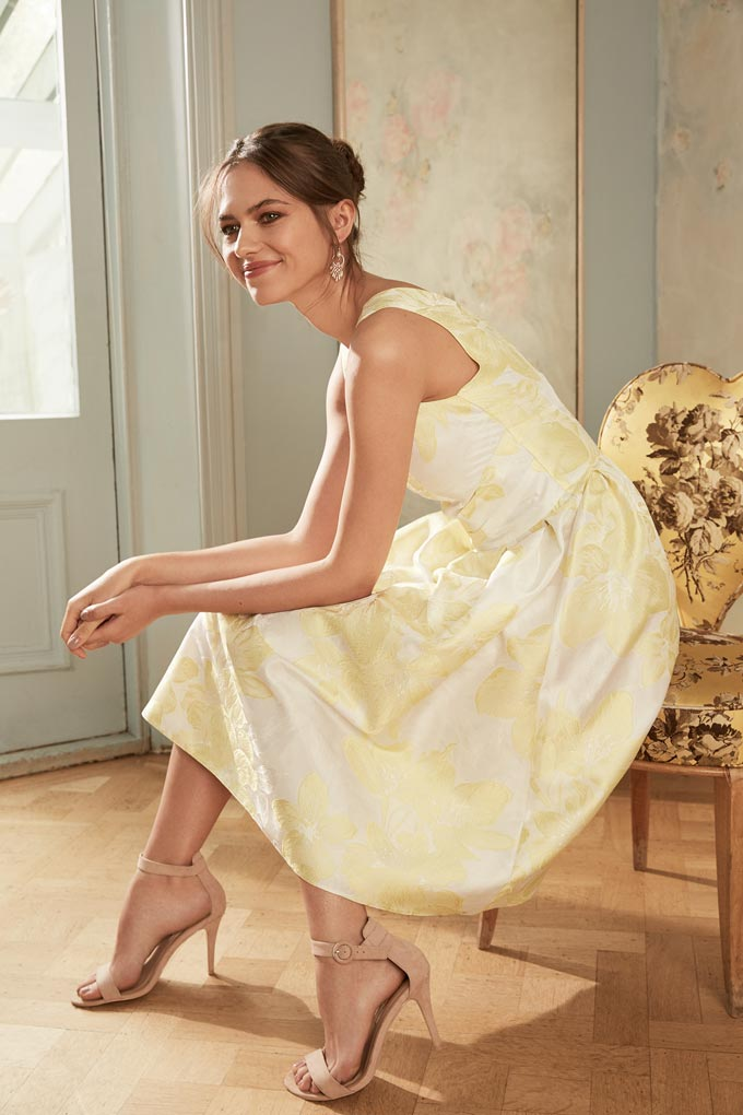 A young beautiful model dressed in a chic midi dress with a pale yellow flower print. Image by Dorothy Perkins.