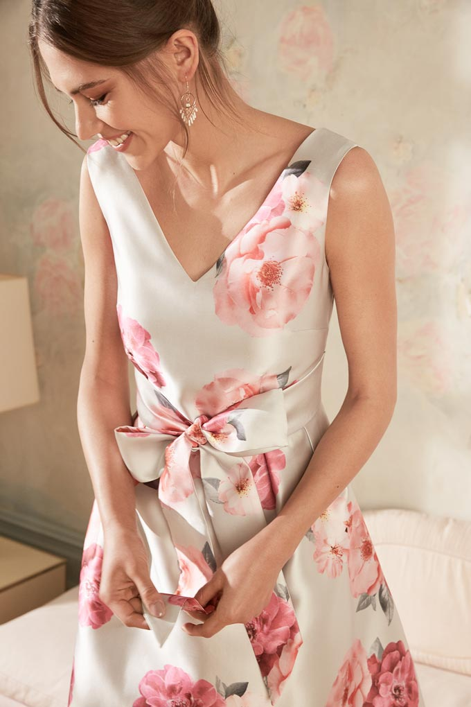 A V neck midi satin dress with a pink floral print worn by a beautiful woman for a wedding. Image by Dorothy Perkins.