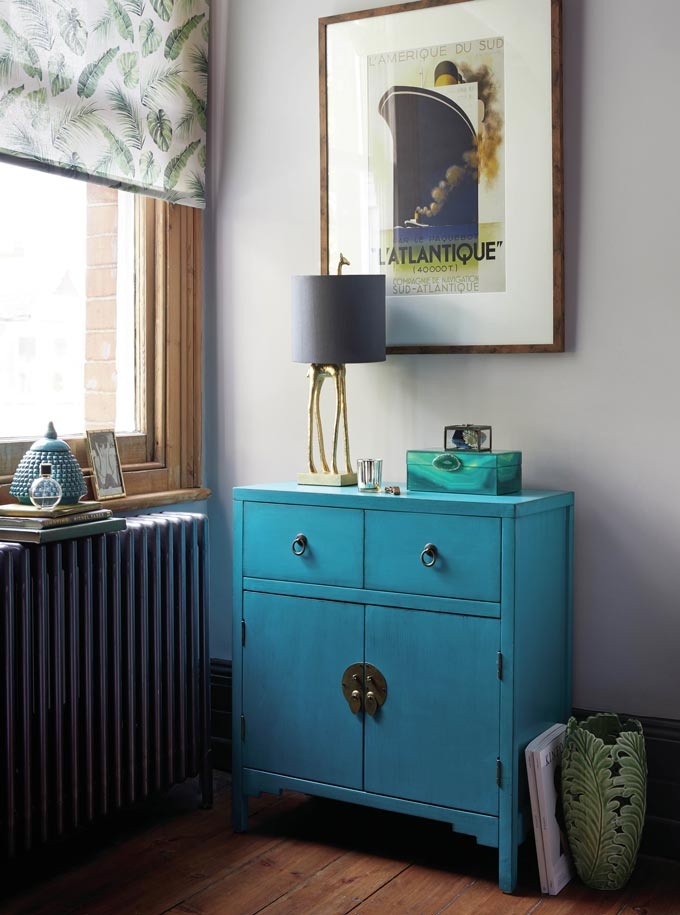 Something very retro about this vignette. A beautiful blue sideboard near a window with a brass table lamp and a navy blue shade and a large print of a boat over it. Image by Dunelm.