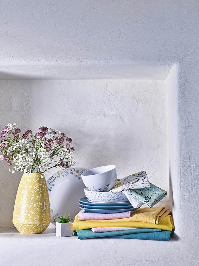 A wall recess in a white - washed wall can look so pretty even with the smallest stuff, like pale blue and yellow soft textiles. Image by George Home.