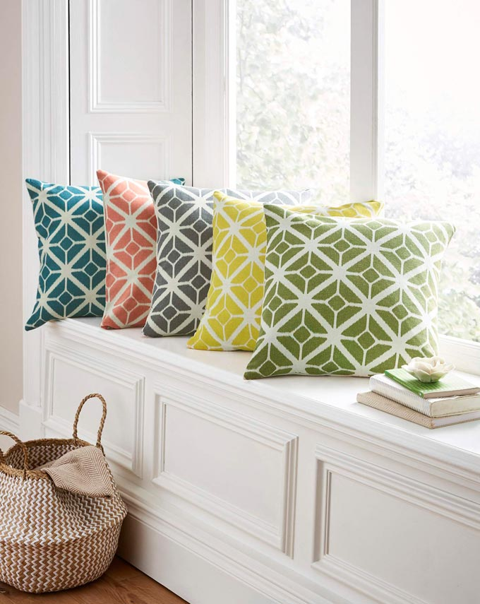 Add a touch of pop colors like with these five pillows with a geometric print pattern by a reading nook next to a big window. Image by House of Bath.