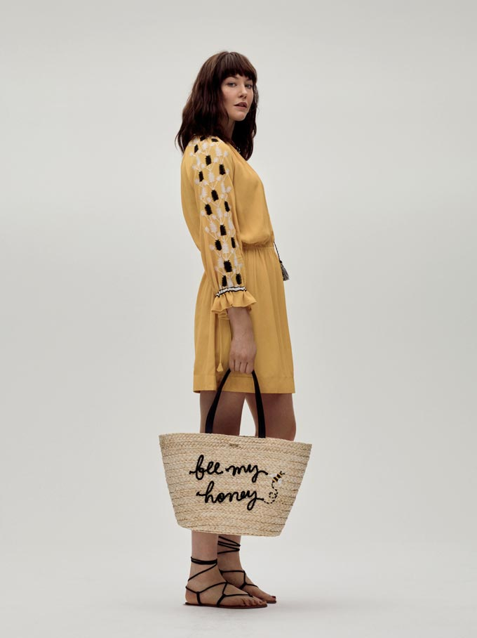 A young model wearing a yellow mini dress and holding a straw bag. Image by House of Fraser.