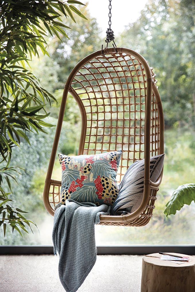 A hanging rattan swing chair creates a great reading nook with a few tropical theme textiles - cocoon perfect! Image by House of Fraser.