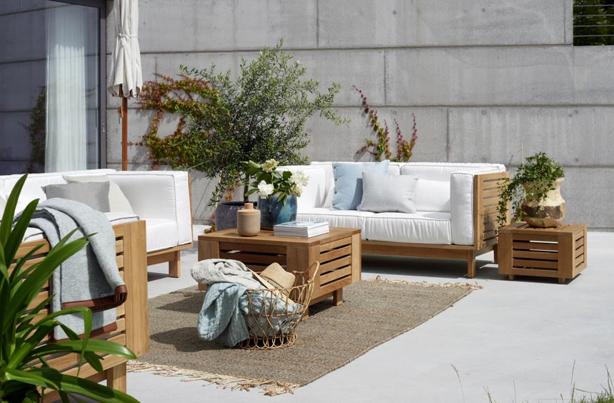 An outdoor setup with sofas, a coffee table and an outdoor area rug.
