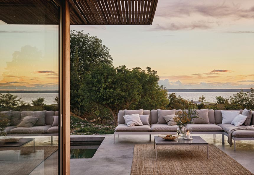 An outdoor sitting setup with a sofa, coffee table and rug create a contemporary stylish setup by a pool. The sea view in the background are compliments of the house. Image by Houseology.