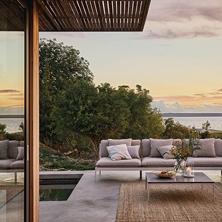 An outdoor sitting setup by a pool with a sofa, coffee table and rug creating a contemporary stylish setup. A dining setup and a day at the far end of the pool complete the outdoor heaven. Image by Houseology.