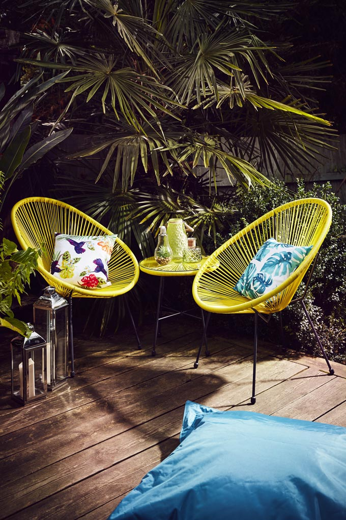 Two yellow string outdoor armchairs on a deck with a side table looking exotic because of the tropical print throw pillows. Image by JDWilliams Home.
