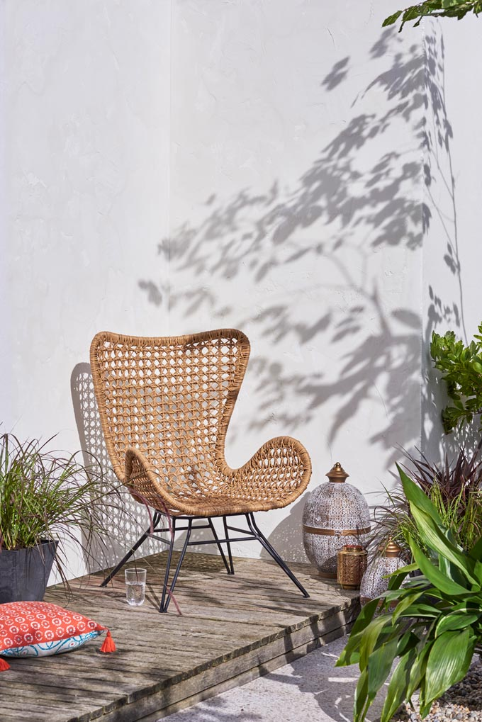 A wicker armchair along with an outdoor lantern makes a stylish little nook for cocooning outdoors. Style is not about size. Image by John Lewis.