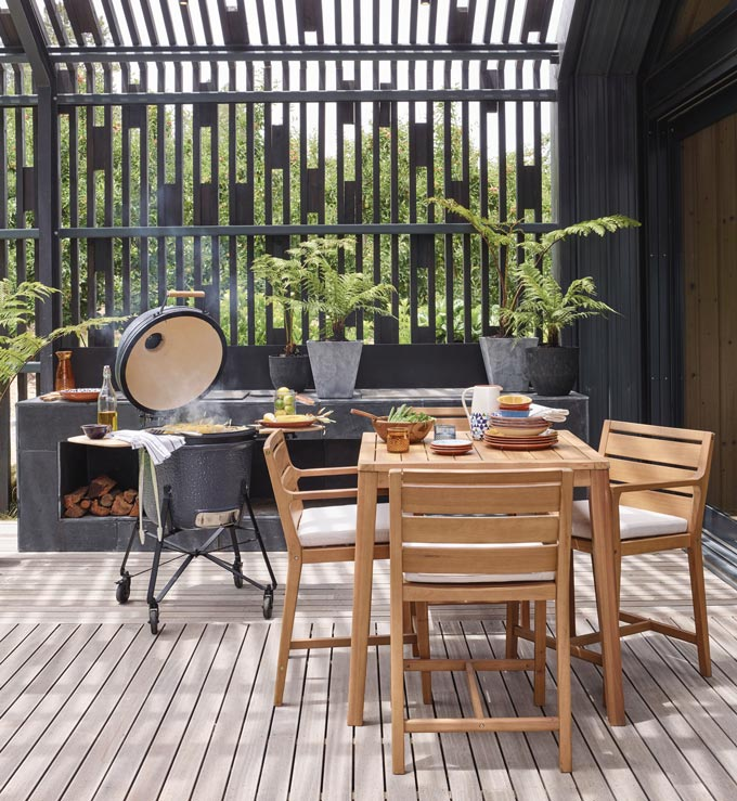 A stylish contemporary dining setup under a pergola with a BBQ on the side for some alfresco cooking. Image by John Lewis.