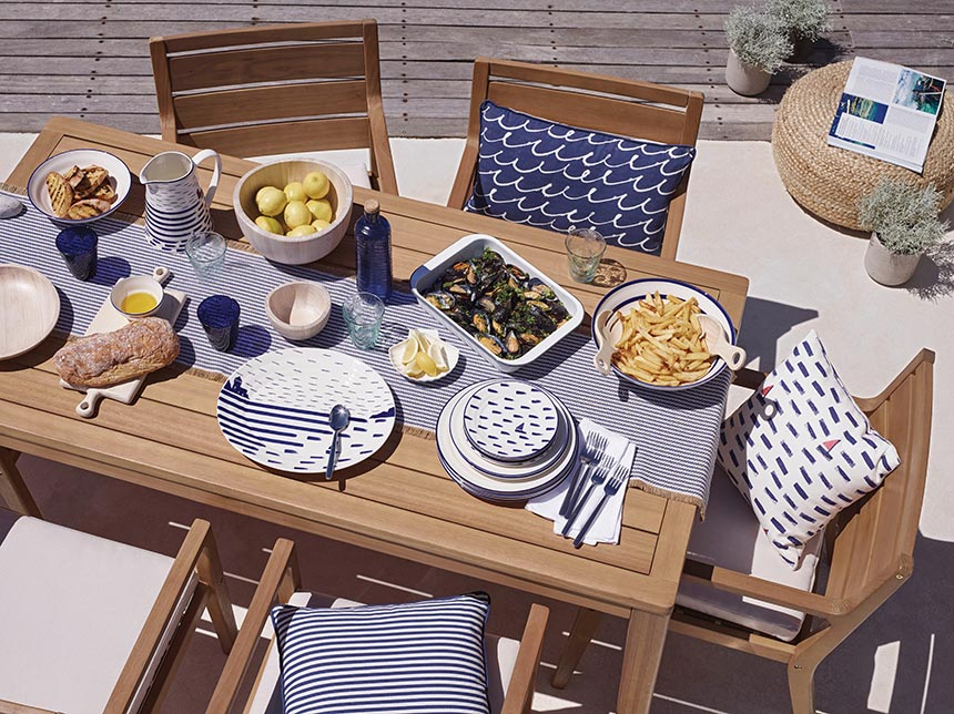 A beautiful outdoor dining setup looks even more summery with nautical themed dinnerware. Image by John Lewis.