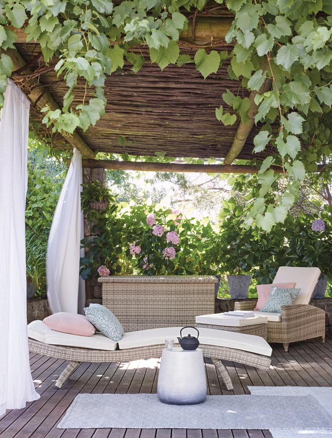 A sunlounger and an armchair under a pergola are the ultimate chill-out furniture. Image by John Lewis.