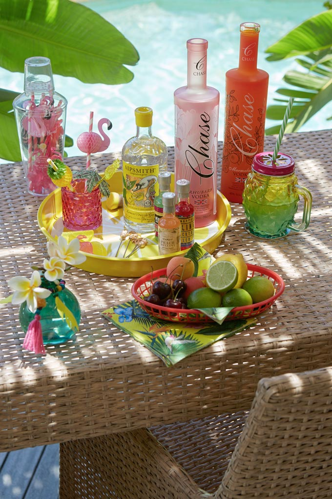 An outdoor tablescape with exotic looking bottles, cocktail glasses, flamingo straws and limes looking all so fresh. Image by John Lewis.