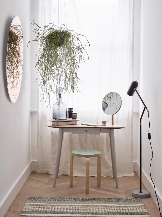 All the essentials in a stylish corner look fabulous in their simplicity. A beautiful boudoir. Round forms, airy furniture, a colored mirror and green foliage all blending in nicely. Image by John Lewis.