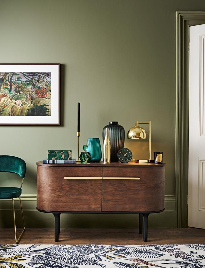 A moody interior with a dark green wall, a jungle theme art print hanging from it, a velvet side armchair besides a gorgeous dark wood sideboard topped with a jungle theme area rug. Image by John Lewis.