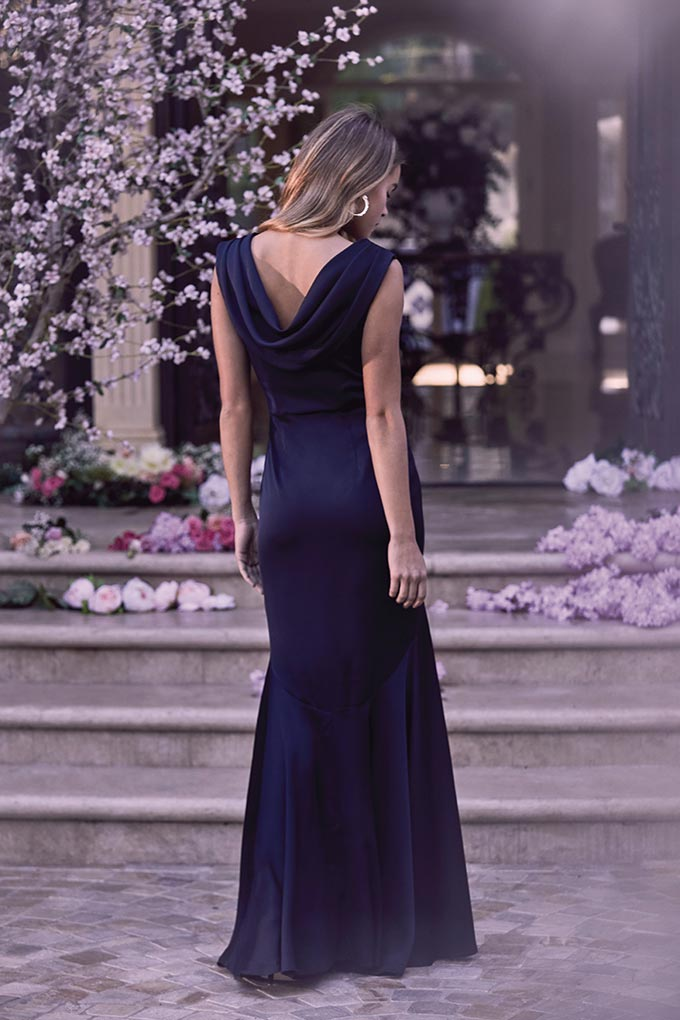 A beautiful model wearing a dark blue maxi dress to a wedding. Image by Lipsy.