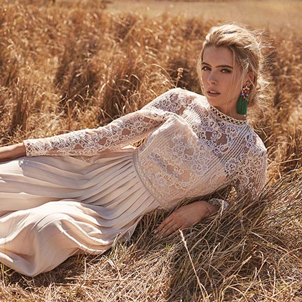 A beautiful blonde woman lying in a hay field wearing a chic guest wedding maxi dress. Image by Little Mistress.