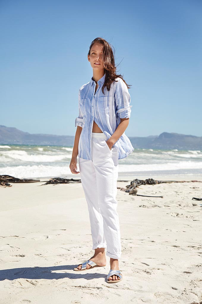 A young woman in a stripe blue linen shirt, white pants and silver flat sliders. Image by M&Co.