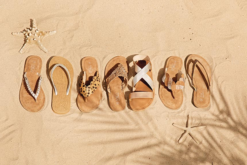 Assortment of flip flops on a sandy beach. Image by M&Co.