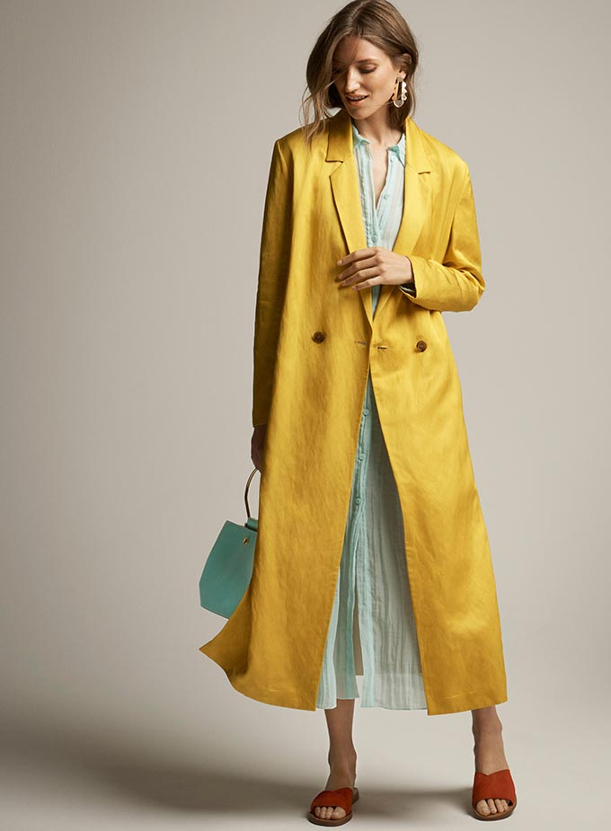 A young model is wearing a soft green pastel dress with matching color handbag, and a yellow trench coat over it. Image by M&S.