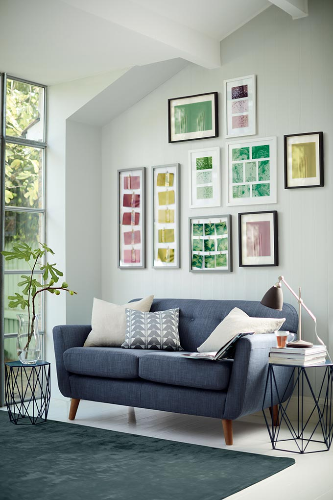 A cool gallery wall with contemporary black frames with images of yellow, or red or green foliage over a dark grey sofa. Looks so fresh and vibrant. Image by Marks and Spencer.