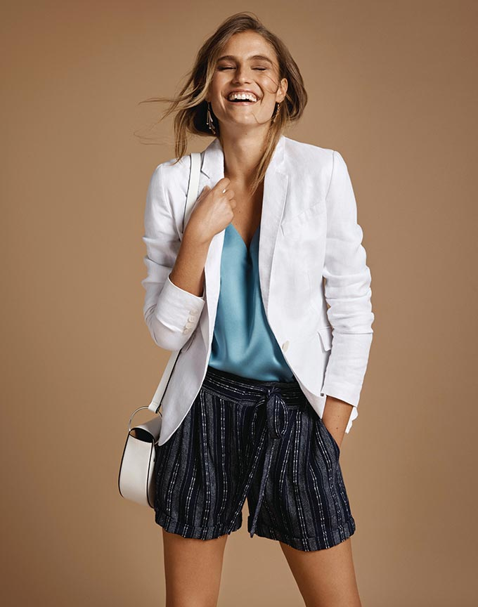 A beautiful stylish woman wearing a white blazer with a blue satin cami underneath it (both high key staples) and black linen shorts under (low key element). Image by Marks and Spencer.