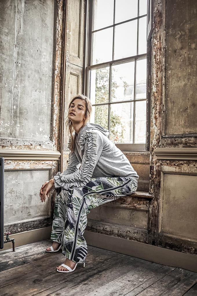 Edgy or what? A stylish woman wearing a grey sweat with wide leg pants that have a tropical print pattern and white sandals. Image by Matalan.