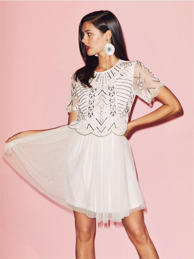 A young beautiful model wearing a white mini dress ideal for a wedding guest because of the geometric pattern of the sequins on the bodice. Image by Miss Selfridge.