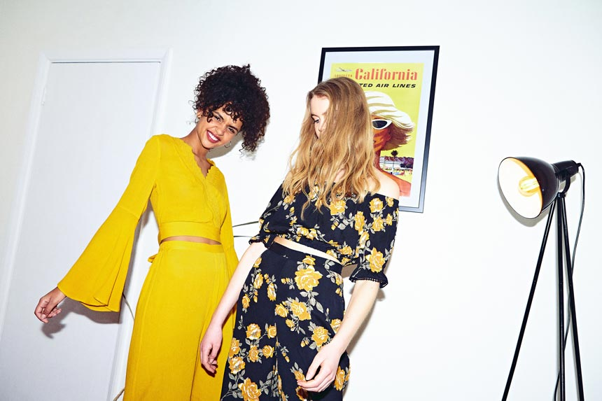 Two young models, one dressed in an all yellow outfit while the other in a black jumpsuit with a yellow flower print. Image by Miss Selfridge.
