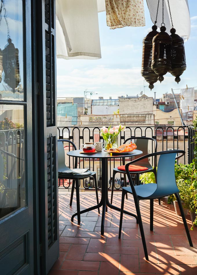 A stylish and modern outdoor dining setup with a small round table in a balcony with a city view. Image by Nest.