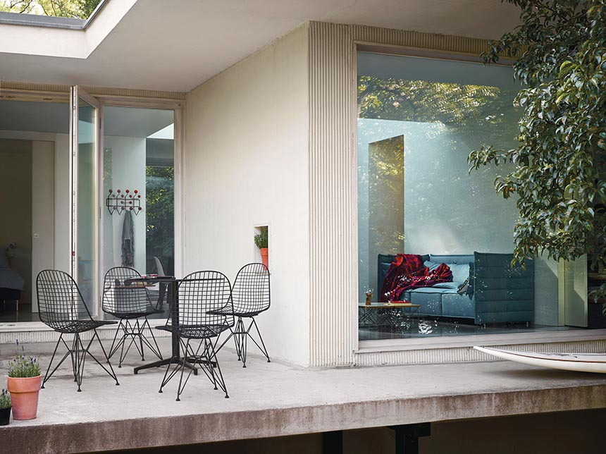 A round table paired with four DKR Wire Chairs - a variation on the iconic one-piece seat shell chairs designed by Charles and Ray Eames. Simple and elegant outdoor seating in this contemporary modern house. Image by Nest.co.uk.