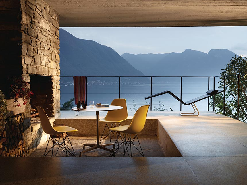 A round table and three yellow Vitra DSR Eames plastic side chairs by an outdoor fireplace with a breathtaking view of a lake is just stunning. Simplicity at its best. Image by Nest.co.uk.