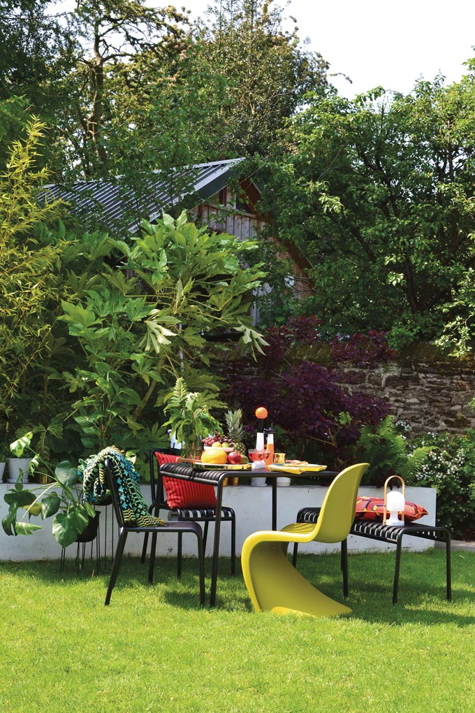A stylish contemporary outdoor setup with a plastic Vitra Panton chair in a bright color matched with black garden furniture designed by Ronan and Erwan Bouroullec. So perfect. Image by Nest.