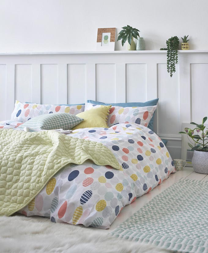 A white bedroom with white bedding that pops up because of its geometric print pattern in blue, yellow and pink color. Image by Next.