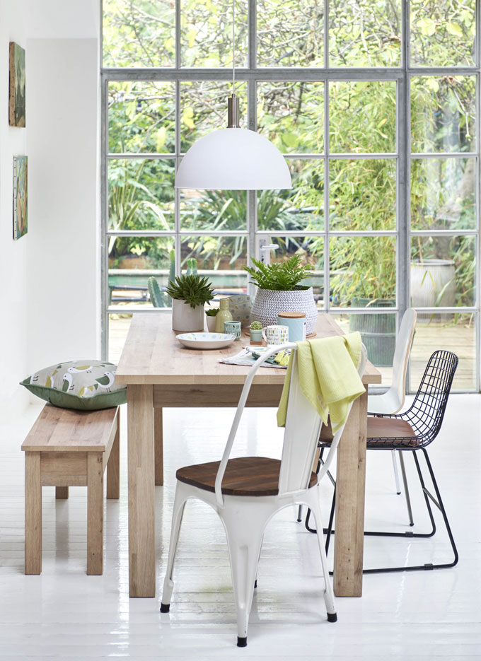 A light, organic dining setup with mismatched chairs and sitting bench that all looks so fresh. Green foliage in the background make everything else pop up. Image by Next.