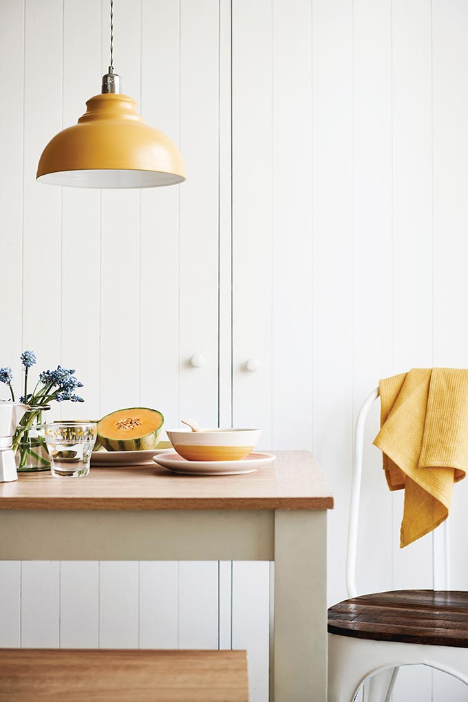 An off white table with a wooden top, a yellow metal pendant light and a yellow tea towel over a white chair fuse in perfectly. Image by Next.