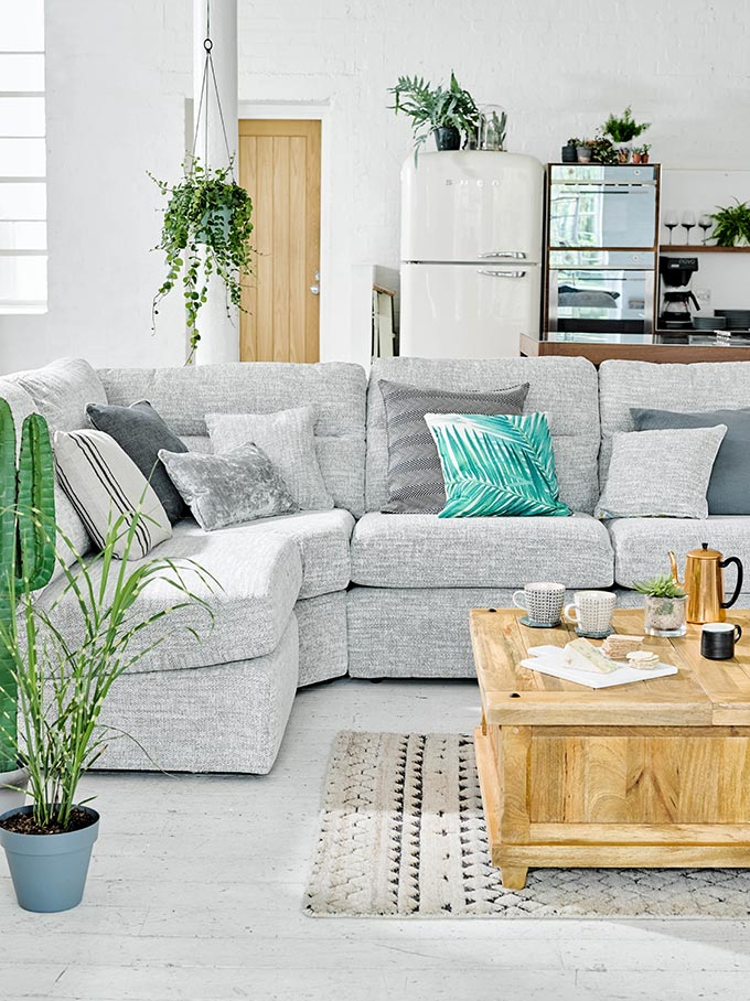 An open floor neutral palette space with a gray sofa in the foreground and a kitchen in the background with pops of green foliage is certainly my cup of tea style! Image by Oakfurnitureland.
