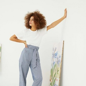 A woman with a white tee and blue high waisted pants leaning against a white wall. Image by Oliver Bonas.