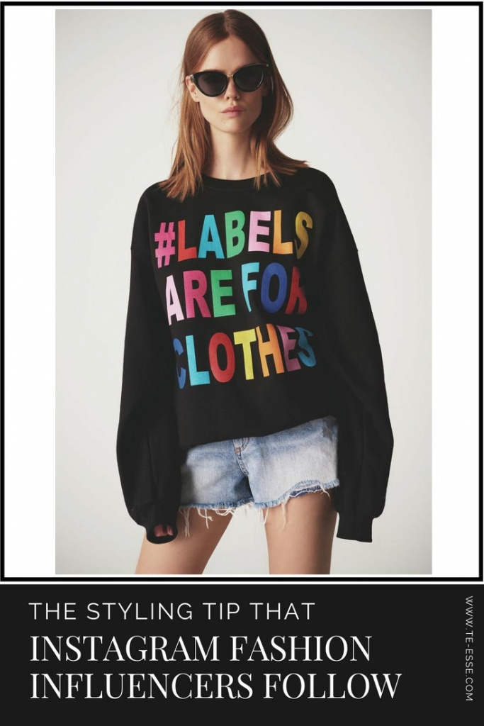 A young girl wearing a black sweat with a colorful print that reads #labels are for clothes, paired with a pair of denim shorts. Image by River Island.