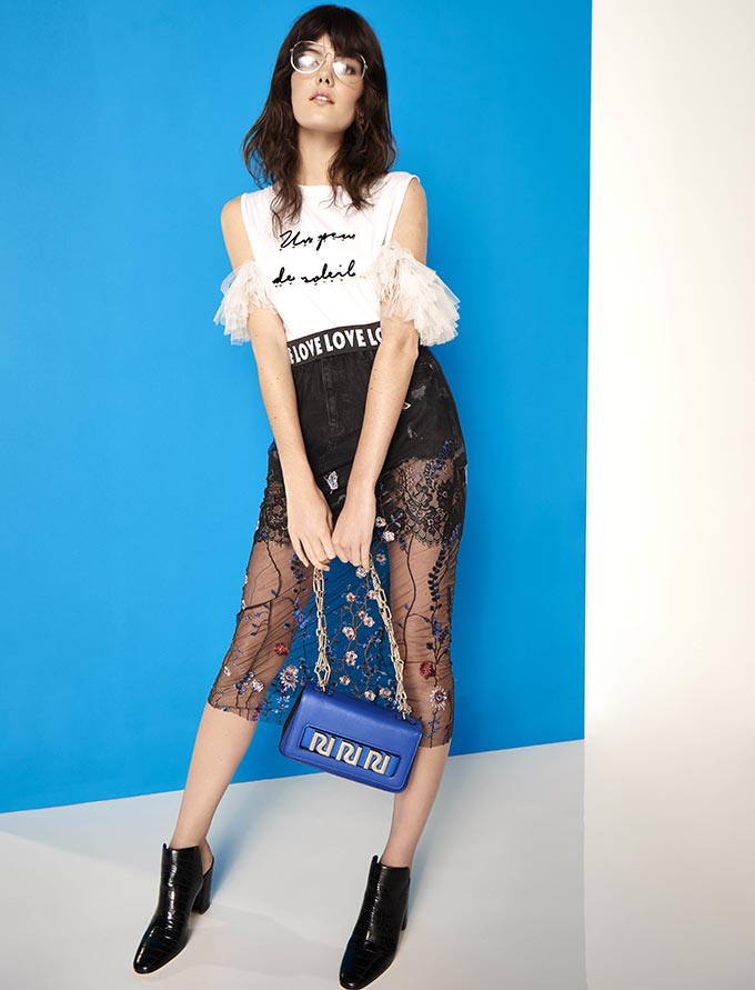 A young woman with a Metropolitan posh style wearing a white tee with a slogan, a mini black skirt with a knee high lace over it, a blue handbag and black sliders. Image by River Island.