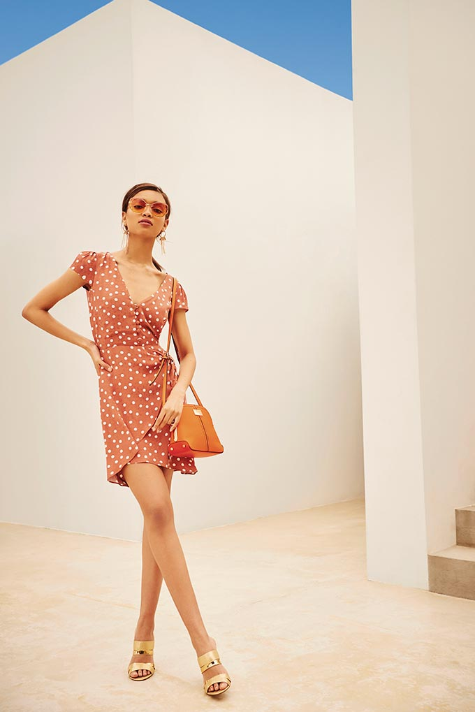 Island ready? A beautiful woman wearing a short muted orange wrap dress with white dots paired with gold metallic high heel sandals. Image by River Island.