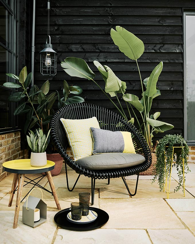 This is a cool outdoor setup with a black string armchair, throw pillows with yellow details and a great side table with a yellow top. The perfect way to add yellow accents in a setup dominated by black hues, organic vibes and greenery. Image by Sainsbury's Home.