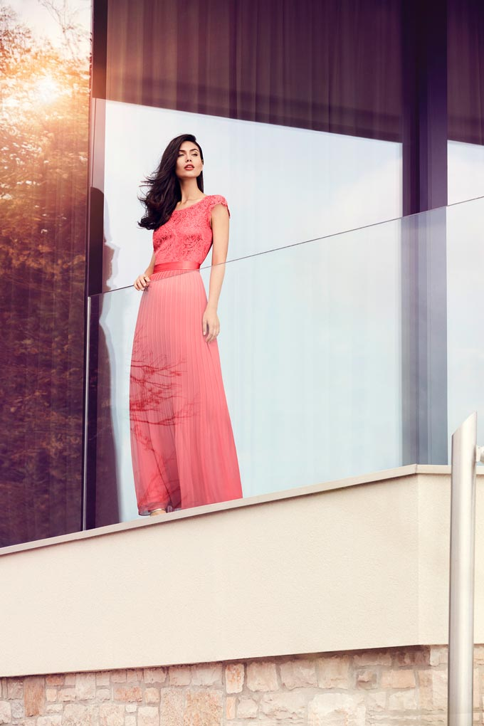 A beautiful model wearing a maxi peach dress and gazing at the view from a balcony. Image by VeraMont.