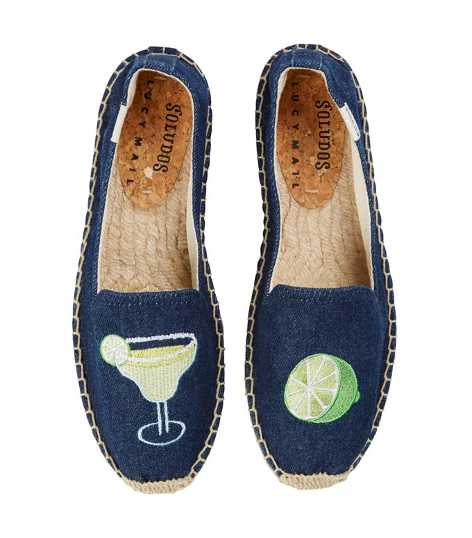 Ideal get in a vacay mood: a pair of navy blue platform slippers with a cocktail glass printed on one them and a half lime on the other. Image by Very Exclusive.