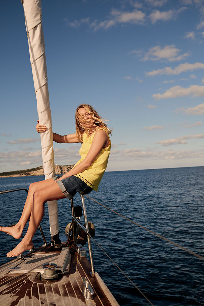 A young woman sitting on the rail of a sail boat is wearing a yellow tango top and denim shorts. Image by Whitestuff.